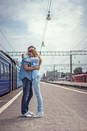 ferrocarril: Pares que abrazan en una estación de tren Foto de archivo