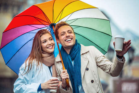 couple in rain: Smiling couple with an umbrella on the street Stock Photo