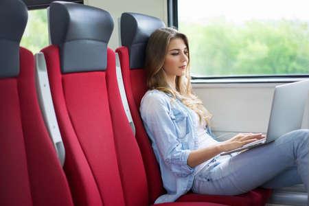 ferrocarril: Mujer joven con un ordenador portátil en el tren