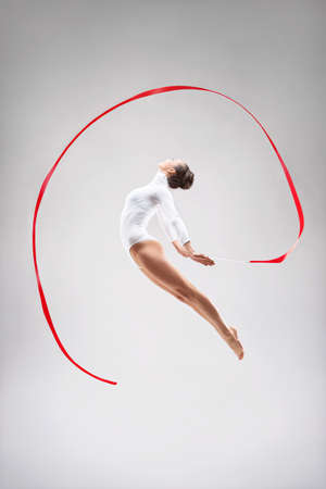 gymnastics: Young gymnast jumping in the studio Stock Photo