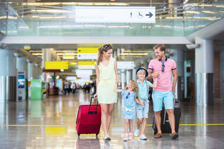 maleta: Familia con ni�os con una maleta en el aeropuerto Foto de archivo