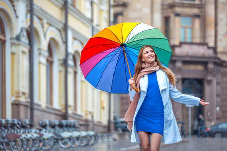 Smiling girl with an umbrella outdoors