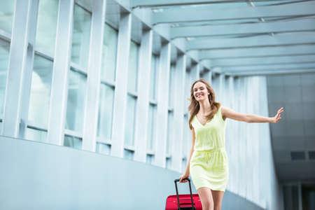 mujer con maleta: La muchacha hermosa con una maleta en el aeropuerto Foto de archivo