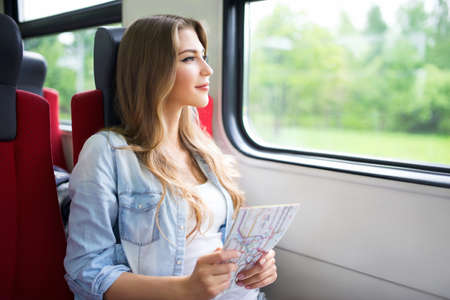 student travel: Young girl with a map of the train Stock Photo