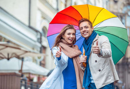 woman with umbrella: Smiling couple with an umbrella