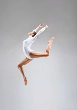 acrobat gymnast: Young gymnast jumping in the studio Stock Photo