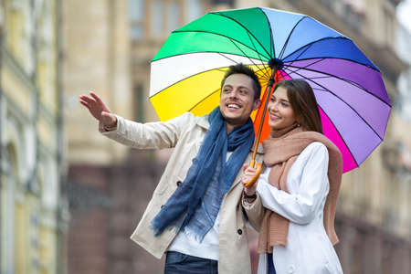 couple in rain: Young couple with an umbrella on the street