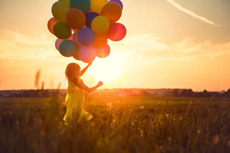 Little girl with balloons in the field