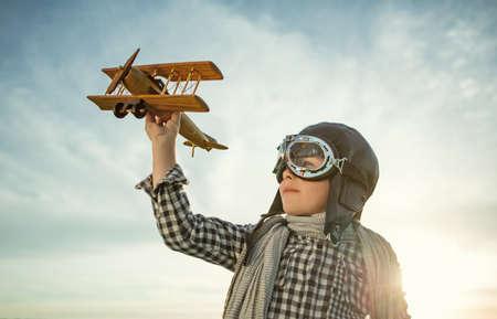 piloto de avion: Niño pequeño con el aeroplano de madera al aire libre