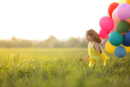 Little girl with balloons outdoors. Stock Photo