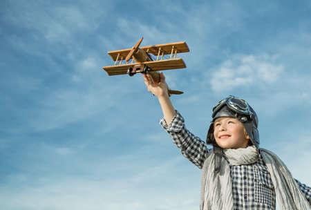 niños sonriendo: Niño feliz con el avión de madera al aire libre