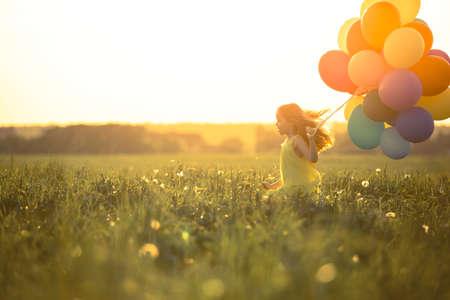 Gelukkig meisje met ballonnen in het veld