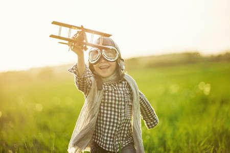 kinder spielen: Kleiner Junge, der mit hölzernen Flugzeug im Freien Lizenzfreie Bilder