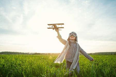 Kleiner Junge, der mit hölzernen Flugzeug auf dem Gebiet Standard-Bild - 46721688