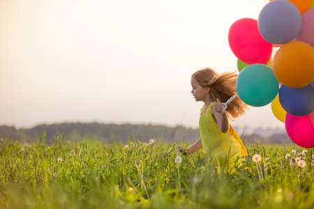 Little girl with balloons outdoors