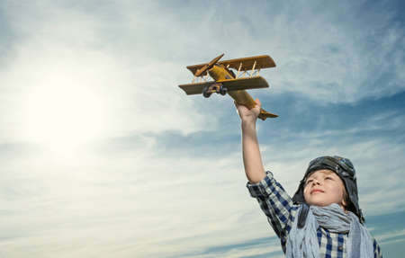 vintage children: Little boy with wooden airplane outdoors