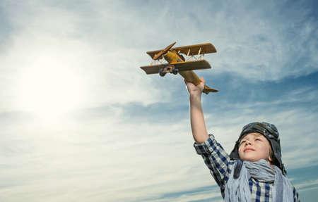 piloto: Niño pequeño con el aeroplano de madera al aire libre