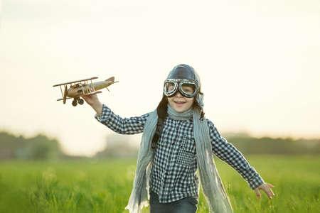 juguetes de madera: Ni�o peque�o con el aeroplano de madera en el campo