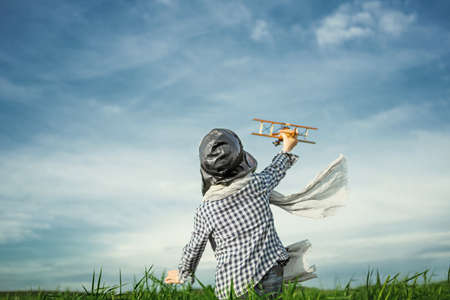 Little boy with wooden airplane in the field Stock Photo