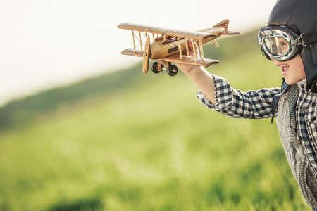 juguetes de madera: Muchacho con el aeroplano de madera en el campo