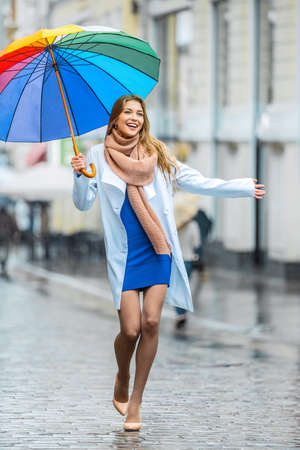 umbrella: Young woman with an umbrella on the street Stock Photo