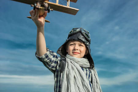 and the air: Little boy with wooden airplane outdoors