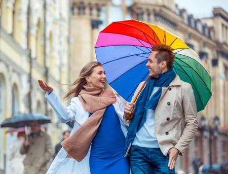 lluvia paraguas: Pareja feliz con un paraguas en la calle