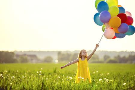 Kleines Mädchen mit Ballonen auf dem Gebiet