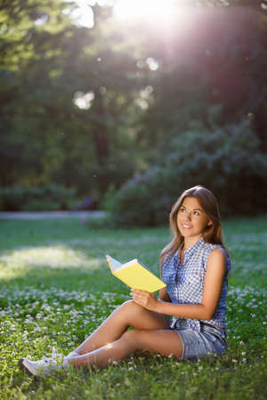 girl studying: Young girl with a book in the park