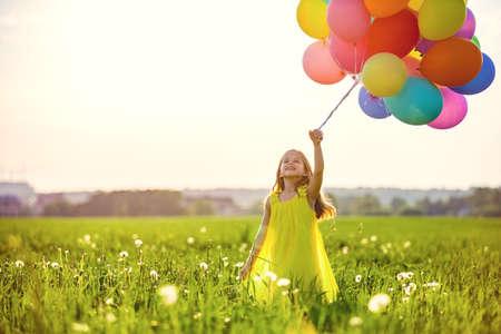 Niña con globos en el campo Foto de archivo