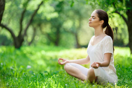 vitality: Young girl in lotus pose in the park