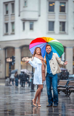 love in rain: Smilig couple with an umbrella outdoors Stock Photo