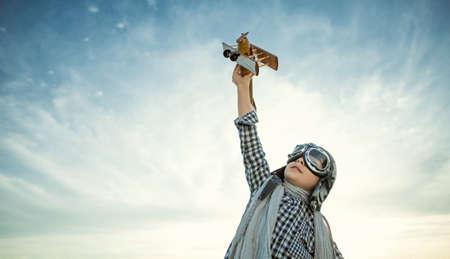pilotos aviadores: Niño pequeño con el aeroplano de madera
