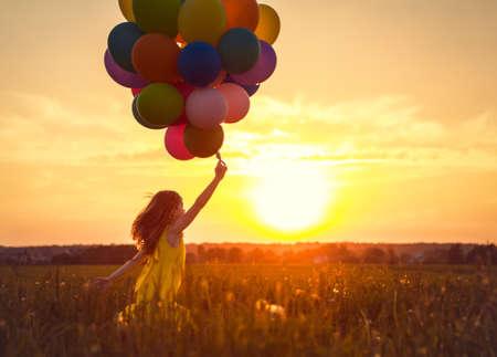 Holčička s balónky na západ slunce Reklamní fotografie - 47018239