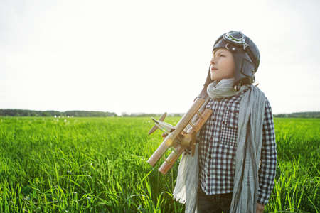 dreamlike: Little boy with wooden airplane outdoors