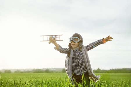 juguetes de madera: Ni�o peque�o con el aeroplano de madera al aire libre