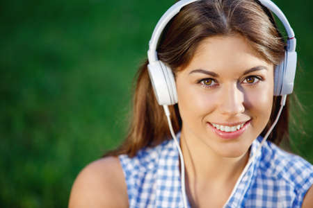 adult woman: Young girl with headphones outdoors