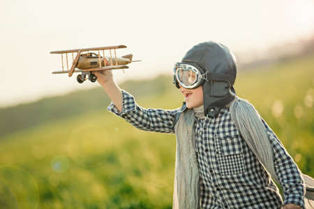 ni�os jugando: Little boy with wooden airplane in the field Foto de archivo