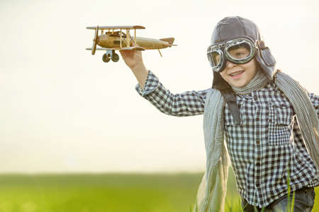 children playing with toys: Little boy with wooden airplane in the field Stock Photo