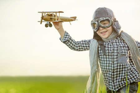 jugando: Niño pequeño con el aeroplano de madera en el campo