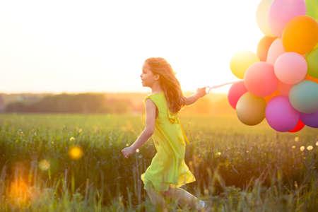 jovenes felices: Ni�a con globos en el campo Foto de archivo
