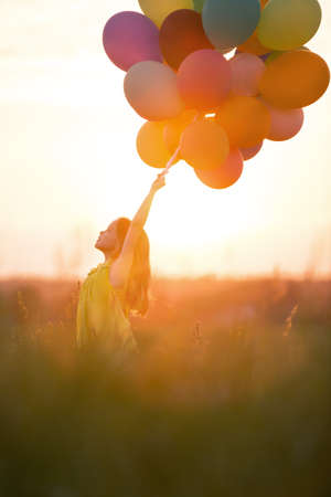 Little girl with balloons outdoors photo