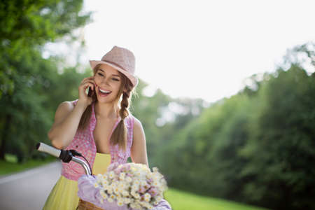 carefree: Beautiful girl on a bicycle talking on the phone Stock Photo