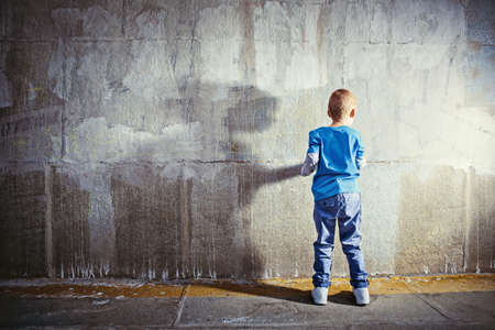 wall paint: Painting little boy outdoors Stock Photo