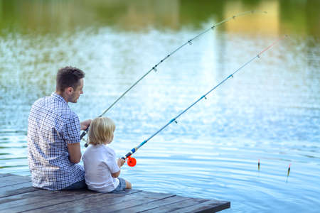 Dad and son fishing at lake