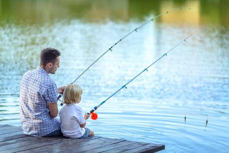 Papa en zoon vissen op het meer