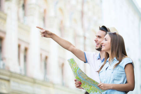 person traveling: Sonriente pareja con un mapa en la calle Foto de archivo