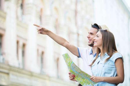 Usmívající se pár s mapou na ulici Reklamní fotografie