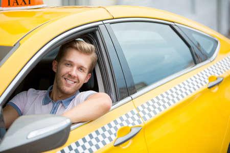 Happy young driver in a taxi Archivio Fotografico
