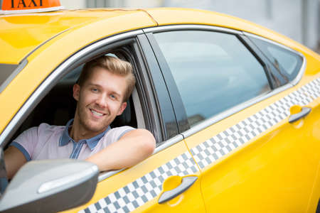Happy young driver in a taxi Stock Photo